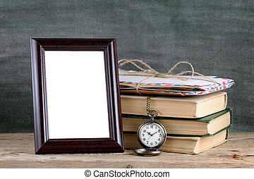 Photo frame and pile of old books on wooden table