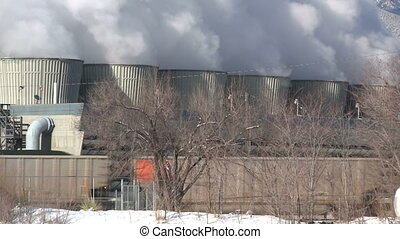 Power plant smoke stacks with train going by