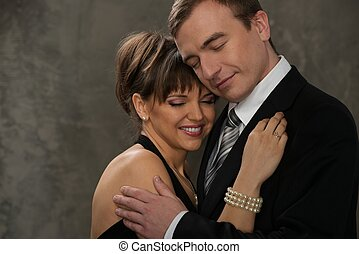 Young  man and woman with closed eyes in elegant evening dress