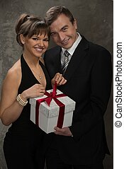 Young smiling man and woman with gift box in elegant evening dress