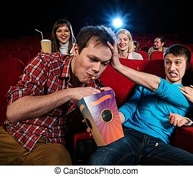 Impudent young man steal popcorn in cinema while people...