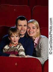 Young man and woman with their child in a cinema