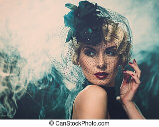 Elegant blond retro woman wearing little hat with veil in...