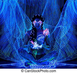 Beautiful woman with body art glowing in ultraviolet light...