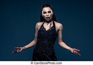 Beautiful vampire style woman in black dress with hands covered in blood