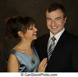 Young well-dressed smiling man and woman in evening dress