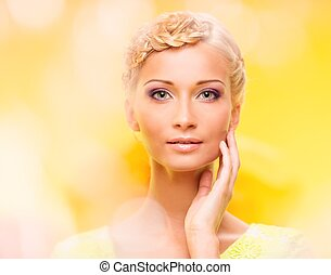 Beautiful young woman with hairdo touching her face with...