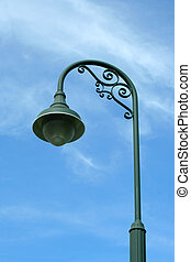 Vitage green lamp post against blue sky