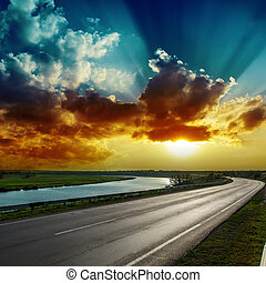 fantastic dramatic sunset over asphalt road