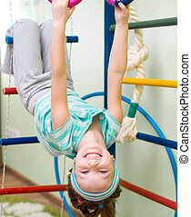 little girl at gymnastic rings - six year old girl playing...