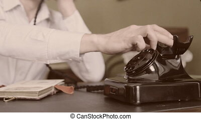 Vintage black telephone. Man dials Sepia