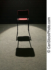 under spotlight - one red chair on stage, lighted with one...
