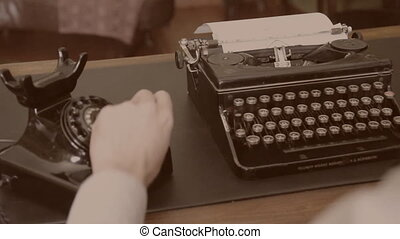 Desk. Vintage typewriter, old phone. Sepia