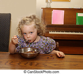 Eating Cereal - Little girl eating cereal with milk - a few...