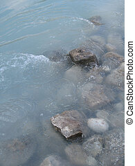 grey polished rocks and green river