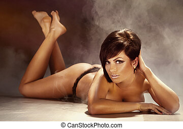Sexy tanned brunette woman lying on the floor, naked -...