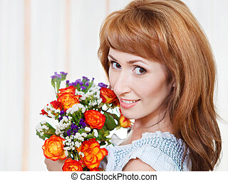 Happy young woman holding bid bouquet of flowers