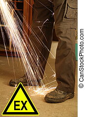 Feets of a worker with sparks of an angle grinder and a sign