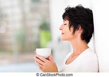 mature woman enjoying a cup of coffee - beautiful mature...