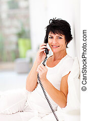 mid aged woman talking on landline phone - happy mid aged...