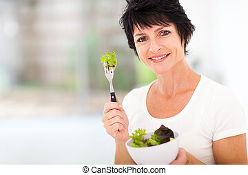 mature woman with fresh green salad