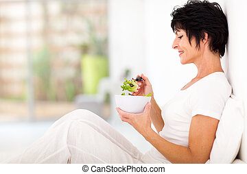 middle aged woman sitting on bed - elegant middle aged woman...