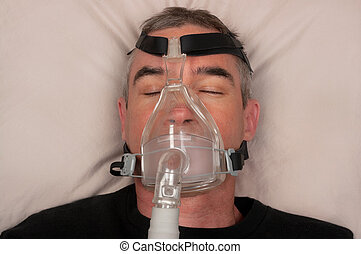 Sleep Apnea and CPAP - Man with sleep apnea and CPAP machine