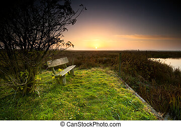bench by river at sunrise