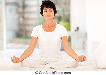 beautiful middle aged woman meditation on bed at home