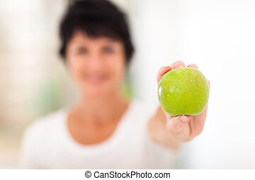 mature woman holding a green apple