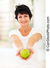 mature woman holding a apple