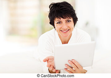 attractive middle aged woman using tablet computer at home