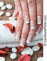 Woman hands with french manicure and flowers on wooden...