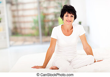 middle aged woman sitting on bed - happy middle aged woman...