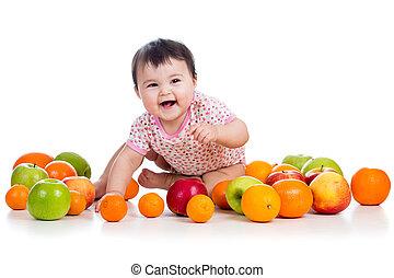 happy baby girl sitting among fresh fruits