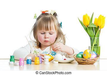 baby girl painting Easter eggs isolated on white background