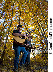Band members play Bluegrass music in the woods.
