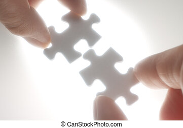 Two person fitting puzzle pieces against the light. - Soft...