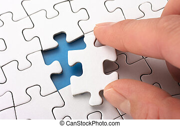 A person fitting the last puzzle piece. - Concept image of...