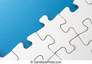 Link of puzzle pieces. - Close-up of puzzle pieces on blue...