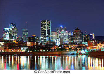 Montreal over river at dusk with city lights and urban...