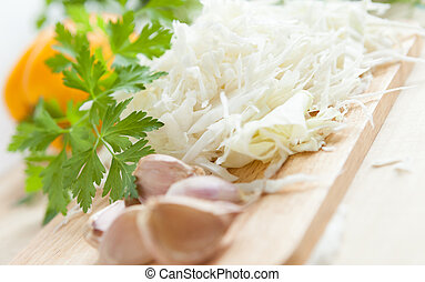 Finely chopped cabbage on wooden board, food closeup