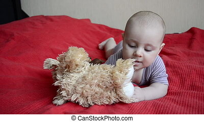 Baby playing with toys on a red
