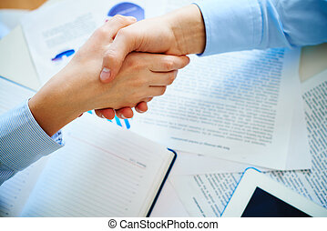 Business deal - Close-up of female and male handshaking over...