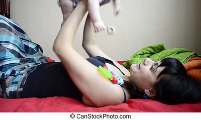 Young mother lying raises the baby