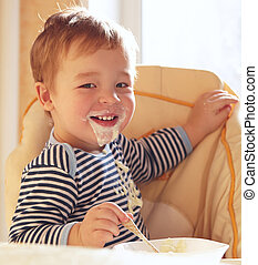 Two year old boy smiles and eating porridge. - Two year old...