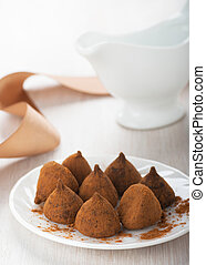 Chocolate truffles on a white plate on the table