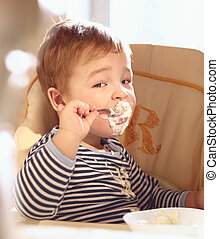 Two year old boy eats porridge in the morning - Portrait of...