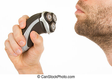 Young man shaving his beard off with an electric shaver