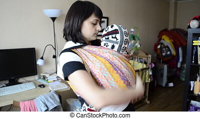 Young mother puts baby in a sling